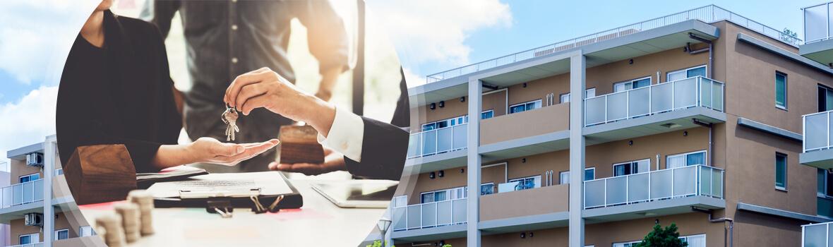鍵を出している不動産スタッフとマンション